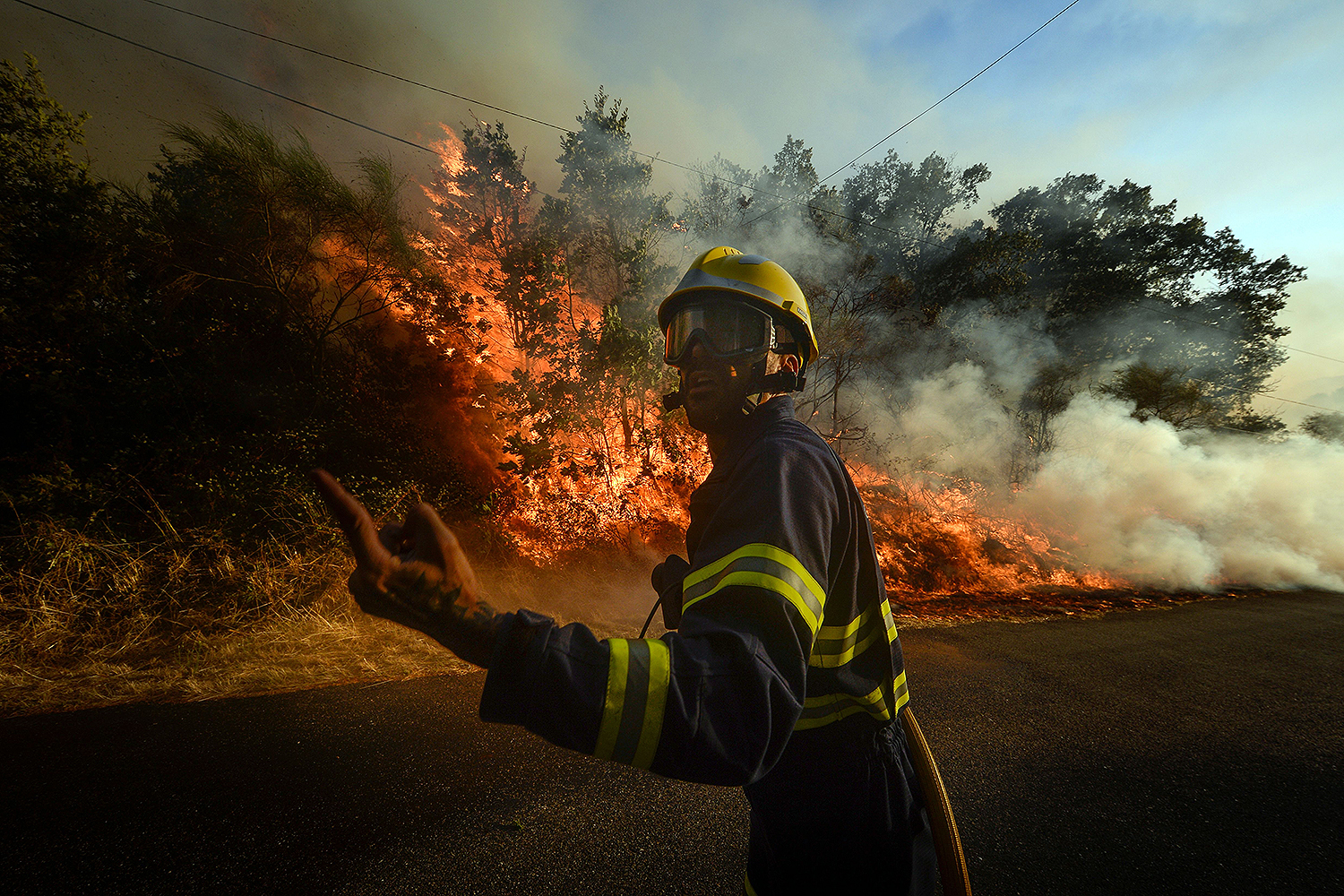 A firefighter motions to a fire squad as a wildfire burns in the village of San Cristobal, Mexico, near Monterrey on July 29. MIGUEL RIOPA/AFP via Getty Images