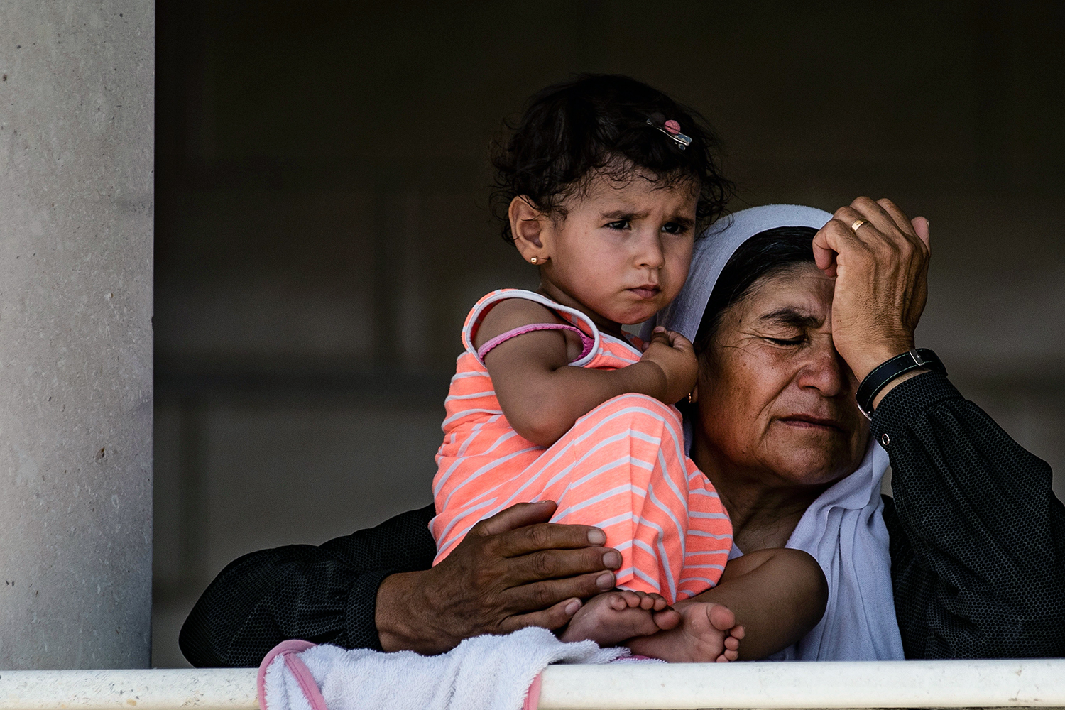 A Syrian woman, who was stranded following a border closure caused by the coronavirus pandemic, waits with a child to cross into Iraqi Kurdistan from the Syrian side of the Semalka border crossing on July 29. DELIL SOULEIMAN/AFP via Getty Images