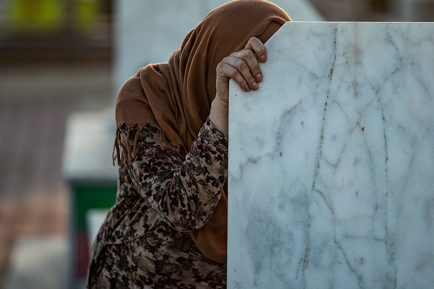 A relative of a slain Kurdish fighter with the Syrian Democratic Forces visits his tomb at a cemetery in the Kurdish-majority city of Qamishli, Syria, on July 30. DELIL SOULEIMAN/AFP via Getty Images