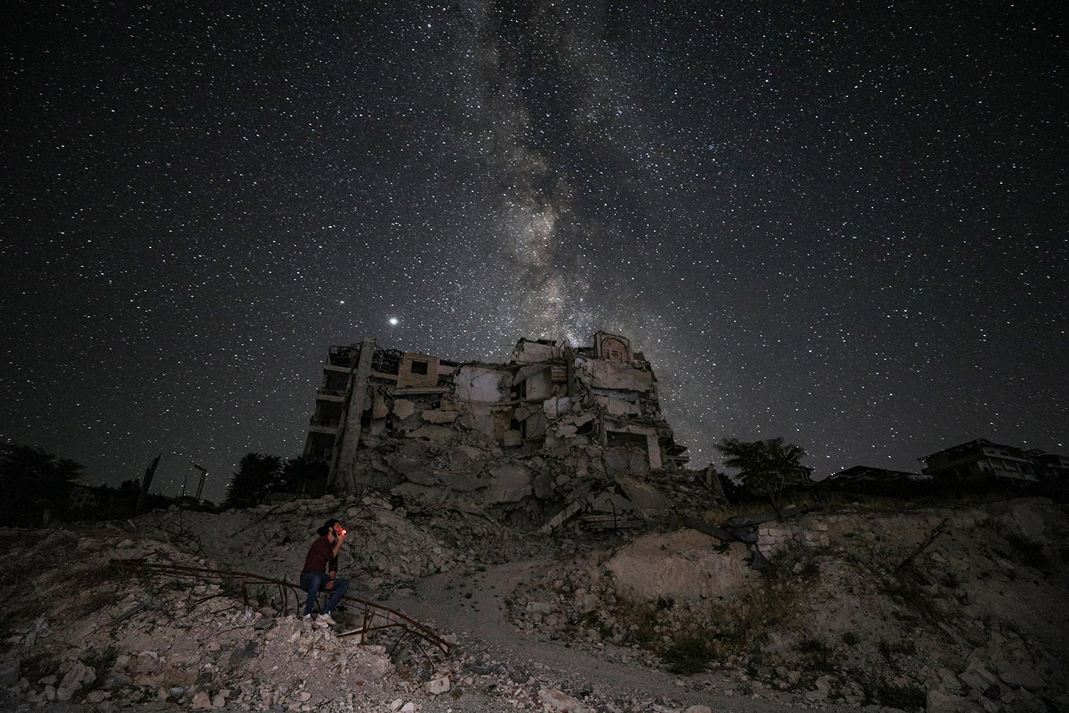 A man smokes near destroyed buildings in the town of Ariha in Syria's rebel-held northwestern Idlib province on June 27 in this long-exposure photograph that showcases the Milky Way galaxy in the night sky above. OMAR HAJ KADOUR/AFP via Getty Images