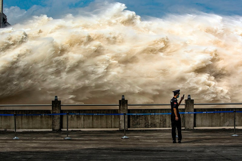 A security guard looks at his phone while water is released from the Three Gorges Dam, a gigantic hydropower project on the Yangtze River, to relieve flood pressure in Yichang, China, on July 19. STR/AFP via Getty Images