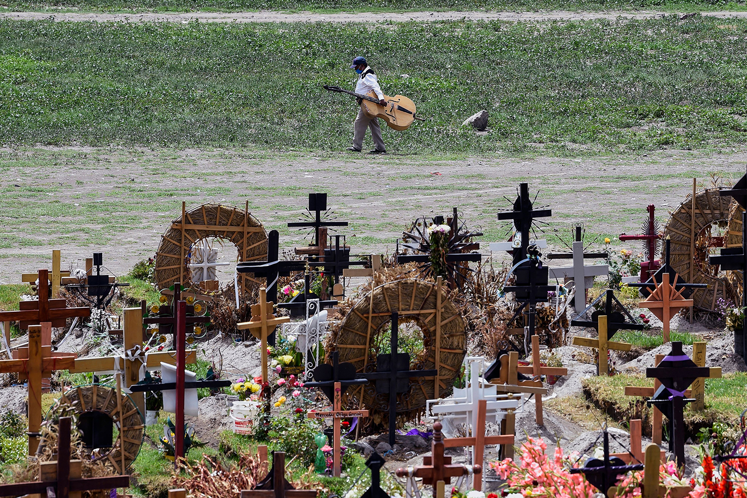 A musician walks past the graves of coronavirus victims in the special area of the Municipal Pantheon of Valle de Chalco, Mexico, on July 28. ALFREDO ESTRELLA/AFP via Getty Images