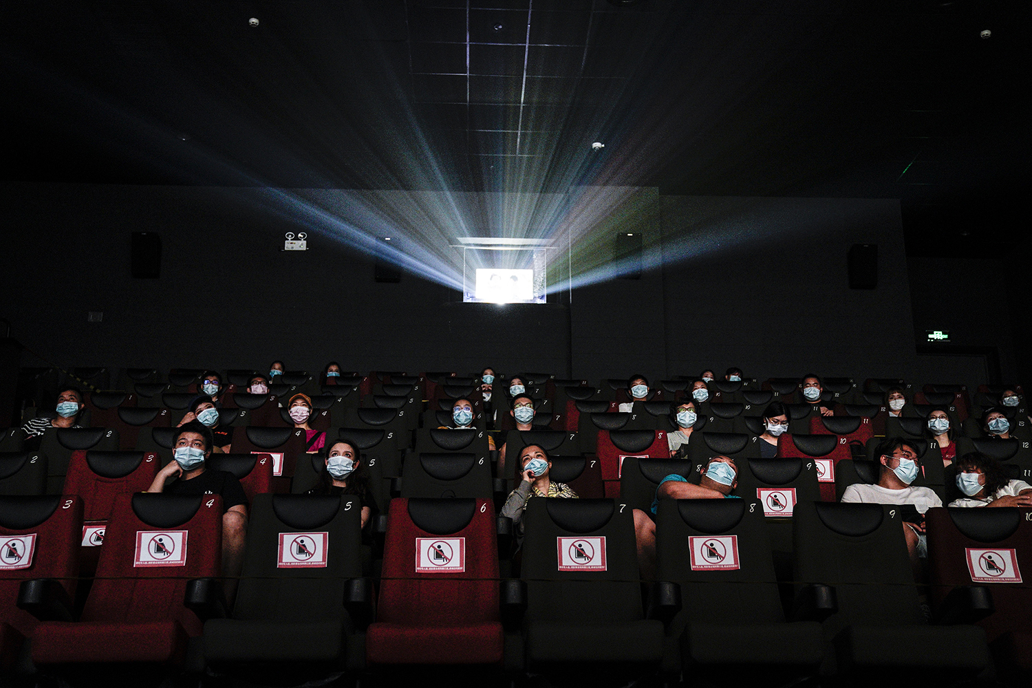 Residents watch a movie in a cinema in Wuhan, China, on July 20. The China Film Administration allowed cinemas in low-risk areas to resume operation with effective epidemic prevention measures in place. Getty Images