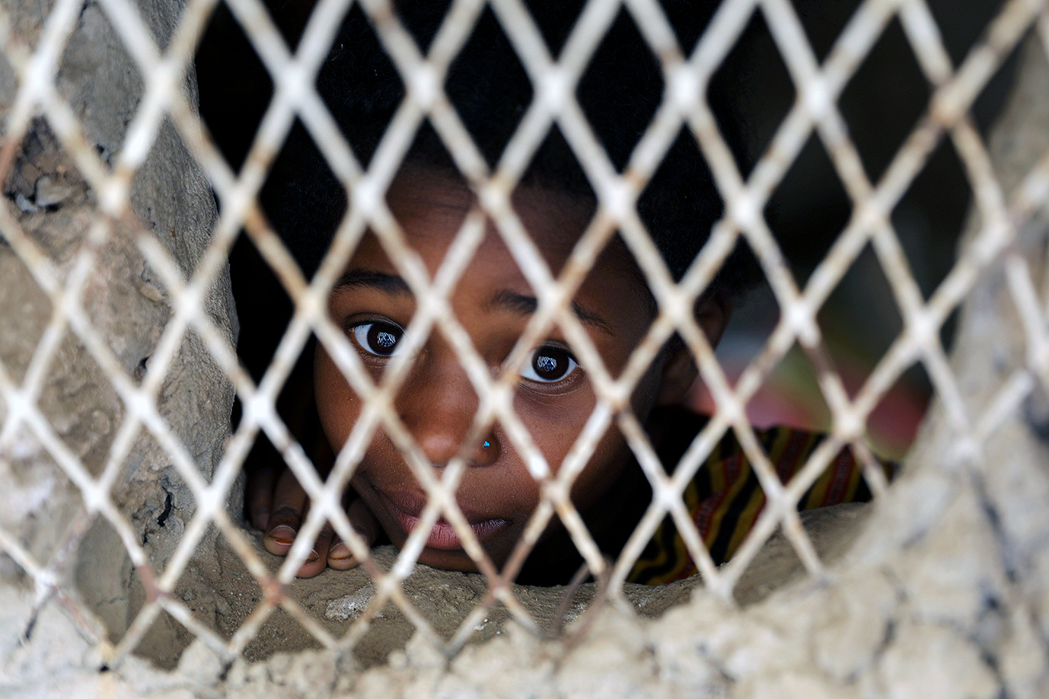 A boy looks out from a window of his family's hut in Sanaa, Yemen, on July 26. Khaled Abdullah/REUTERS