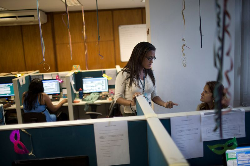A call center supervisor talks with a telemarketing co-worker in Rio de Janeiro on Feb. 5, 2013.