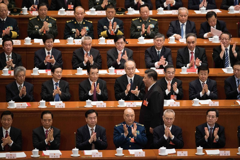Delegates applaud as China's President Xi Jinping walks past during the closing session of the National People's Congress at the Great Hall of the People in Beijing on March 20, 2018.