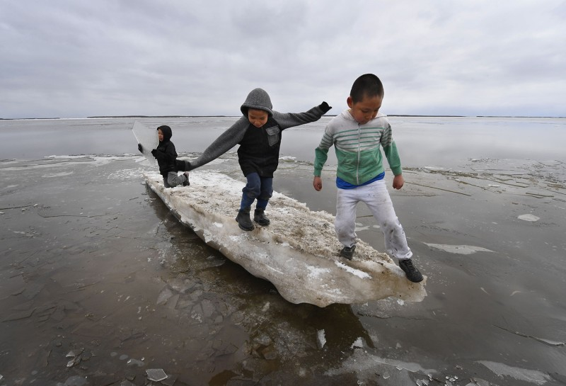 Schoolchildren play on melting ice in the climate change-affected Yupik Eskimo village of Napakiak in Alaska on April 18, 2019.
