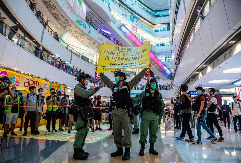 Riot police hold up a warning flag during a demonstration in a mall in Hong Kong on July 6, in response to a new national security law introduced in the city that makes political views, slogans, and signs advocating Hong Kong's independence or liberation illegal.