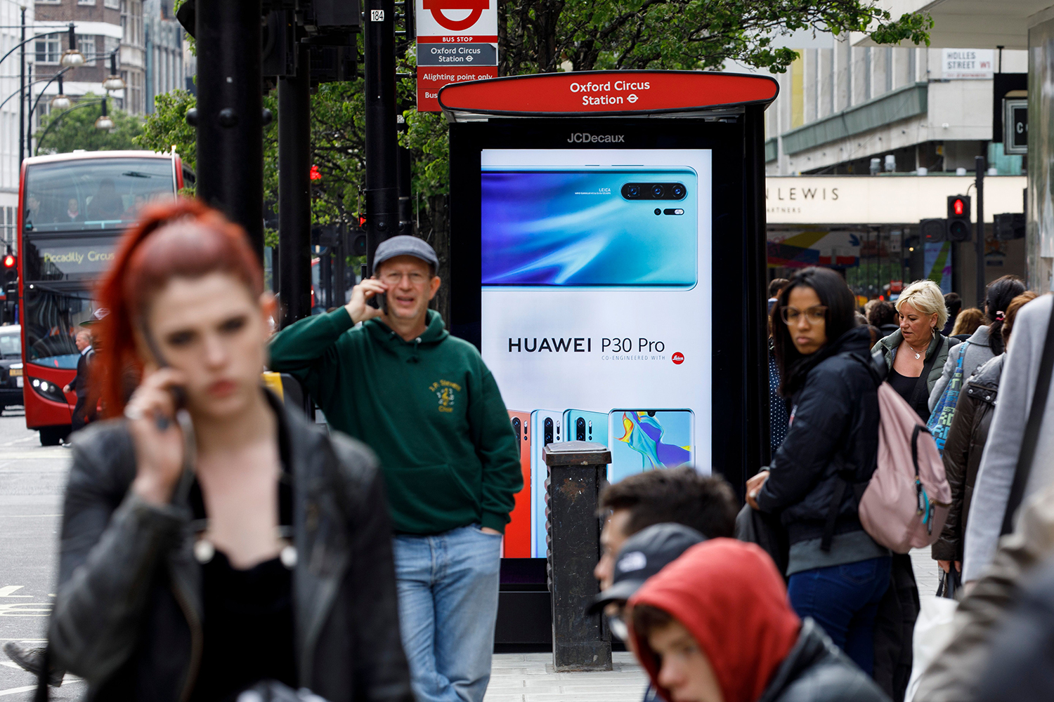 Pedestrians use their cell phones near a Huawei advertisement at a bus stop in central London on April 29, 2019.