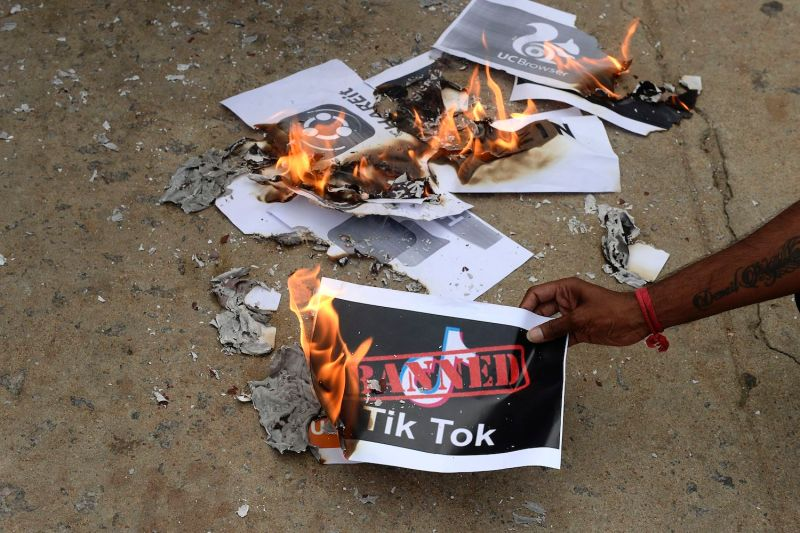 People burn posters with the logo of the Chinese- owned video-sharing app TikTok in Hyderabad, India, on June 30.
