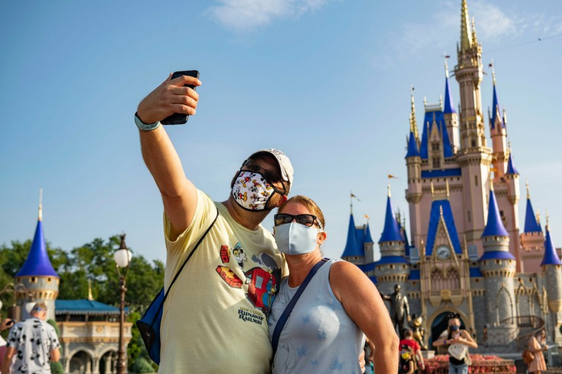 Guests stop to take a selfie at Walt Disney World Resort in Orlando, Florida on the first day of the theme park's reopening on July 11, 2020.