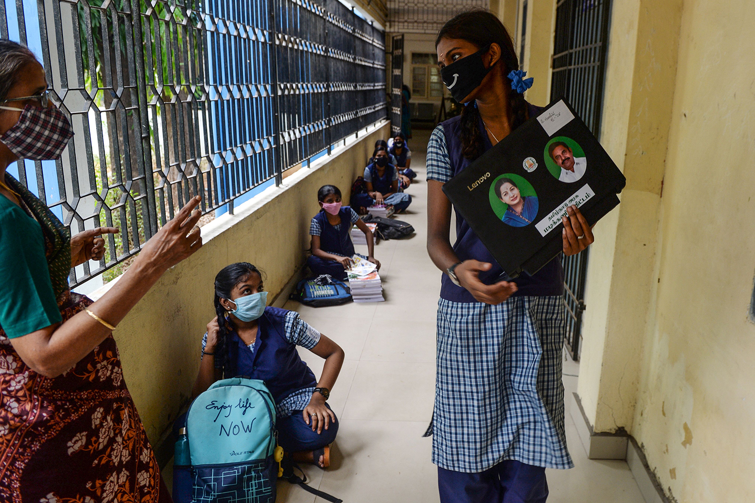 A student carries a laptop to download study materials as others line up to collect textbooks before a telelearning class at their home in Chennai on July 15.