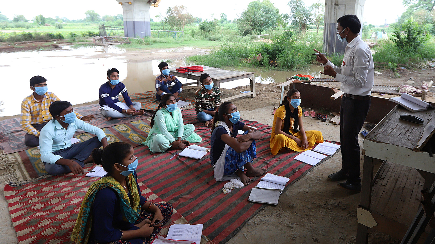 A college student teacher conducts open-air classes in a slum for underprivileged students who lack electronic devices to attend online classes as schools remain closed in New Delhi on July 20.