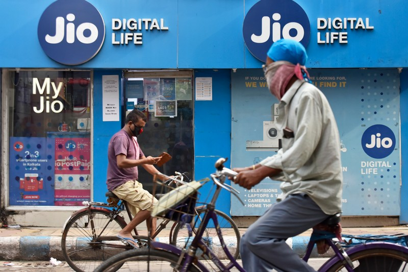 Cyclists pass a Jio store in Kolkata on July 13, 2020.