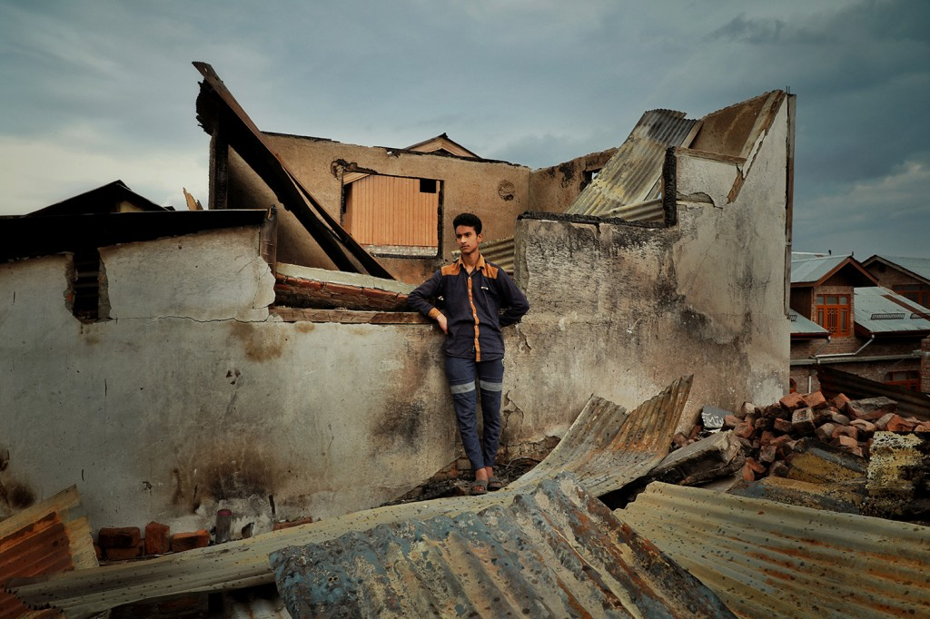 Seventeen-year-old Mohammad Ibrahim stands in the remains of his home in Srinagar on May 29.