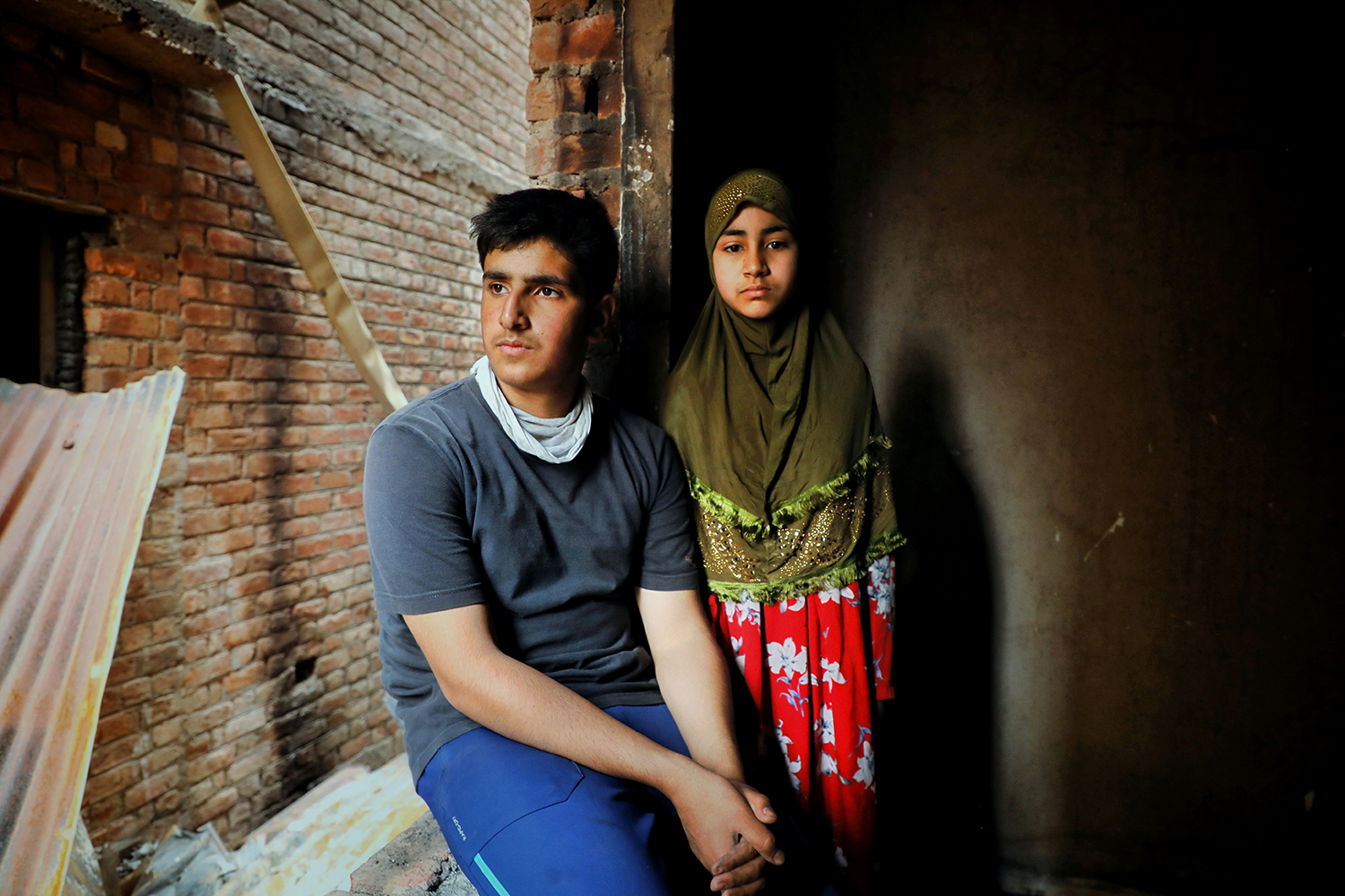Salik Gandroo and his sister Safoora take a break while sanitizing the remains of their home in Srinagar on May 29.