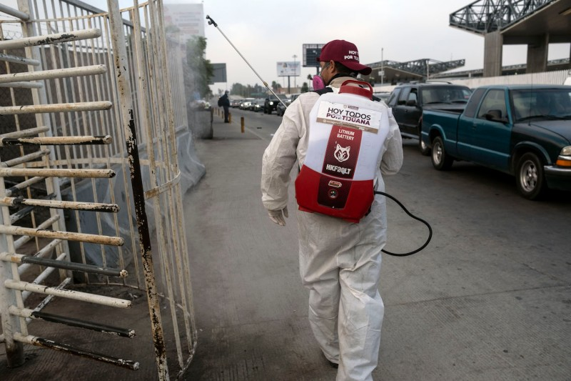 A municipal worker sprays disinfectant to prevent the spread of the COVID-19, as commuters wait to cross the U.S.-Mexican border in Tijuana, Mexico on July 7.