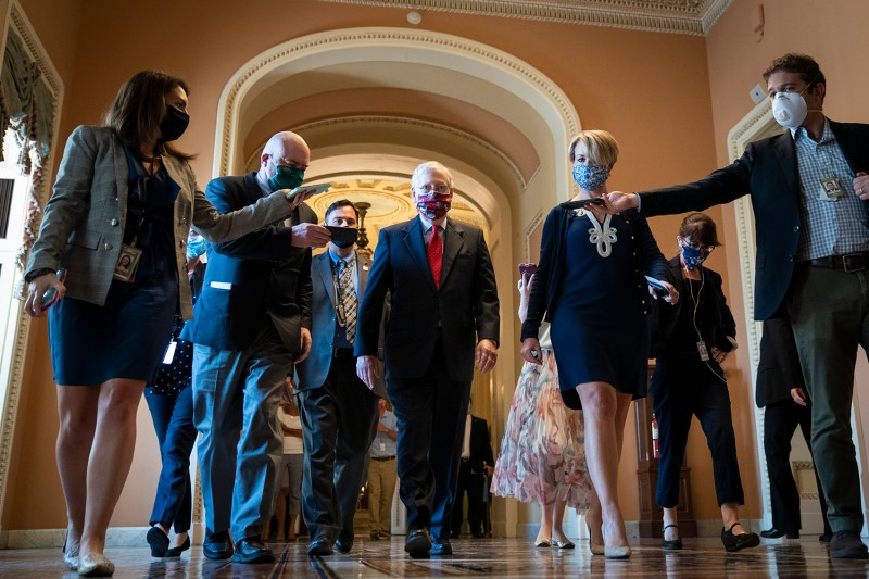 U.S. Senate Majority Leader Mitch McConnell is swarmed by reporters as he leaves the Senate floor on July 30 in Washington. Republicans and Democrats in the Senate remain in a stalemate as the the $600-per-week federal unemployment benefit is set to expire on Friday.