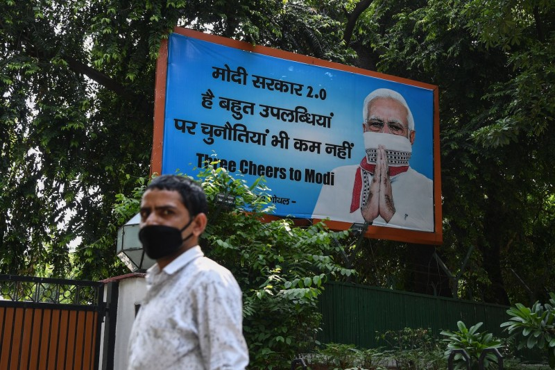 A man stands in front of a billboard displaying an image of Indian Prime Minister Narendra Modi wearing a scarf as a facemask.