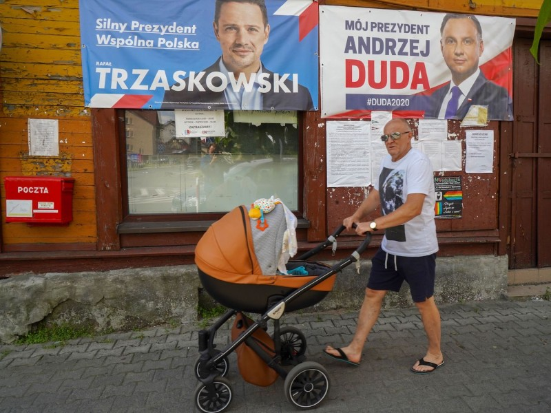 A man pushes a stroller past campaign posters of Warsaw Mayor and candidate in Poland's presidential election, Rafal Trzaskowski and of President Andrzej Duda on July 9, 2020 in Raciaz, Poland, ahead of the July 12, 2020 presidential election.