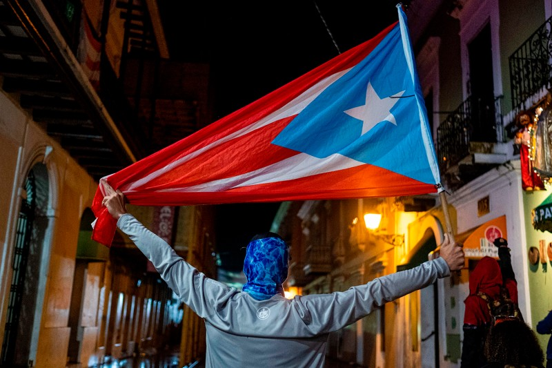 A protester holds a Puerto Rican flag during a demonstration against Puerto Rico's government in front of the governor's mansion in San Juan, Puerto Rico on Jan. 23.
