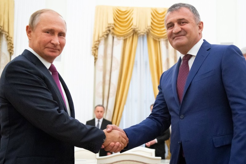 Russian President Vladimir Putin and Anatoly Bibilov, the leader of Georgia's breakaway region of South Ossetia, shake hands prior to their meeting in the Kremlin.