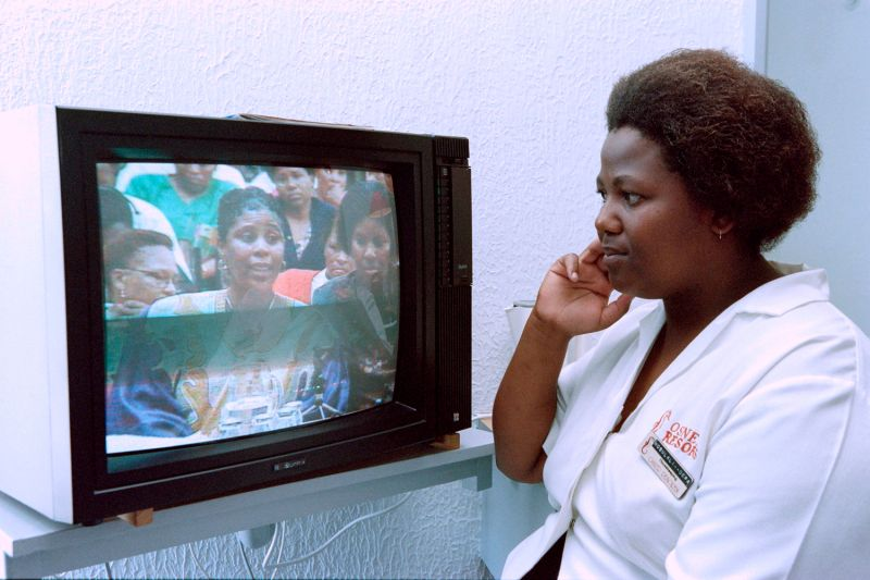 A hotel cleaner listens during a live telecast of the start of the Truth and Reconciliation Commission in South Africa