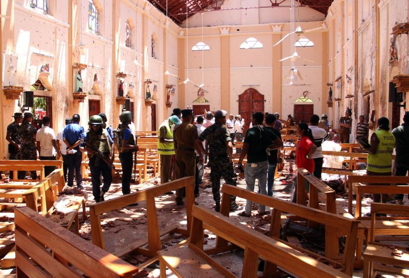 TOPSHOT - Sri Lankan security personnel walk through debris following an explosion in St Sebastian's Church in Negombo, north of the capital Colombo, on April 21, 2019. - A series of eight devastating bomb blasts ripped through high-end hotels and churches holding Easter services in Sri Lanka on April 21, killing nearly 160 people, including dozens of foreigners. (Photo by STR / AFP) (Photo credit should read STR/AFP via Getty Images)