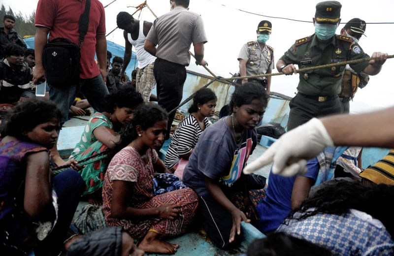 Sri Lanka migrants bound for Australia remain on their boat despite it being washed ashore.