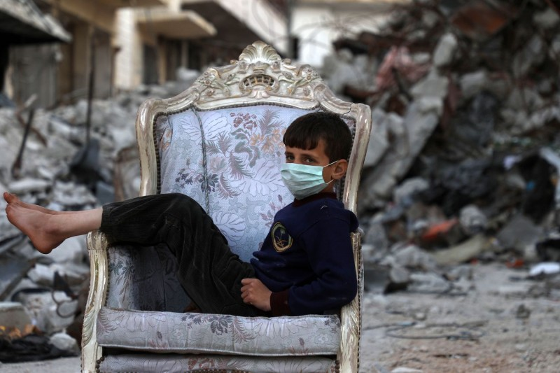A child sits on a couch found in a street, ravaged by pro-regime forces air strikes, in the town of Ariha in the southern countryside of the Idlib province on April 11, 2020. (AAREF WATAD/AFP via Getty Images)