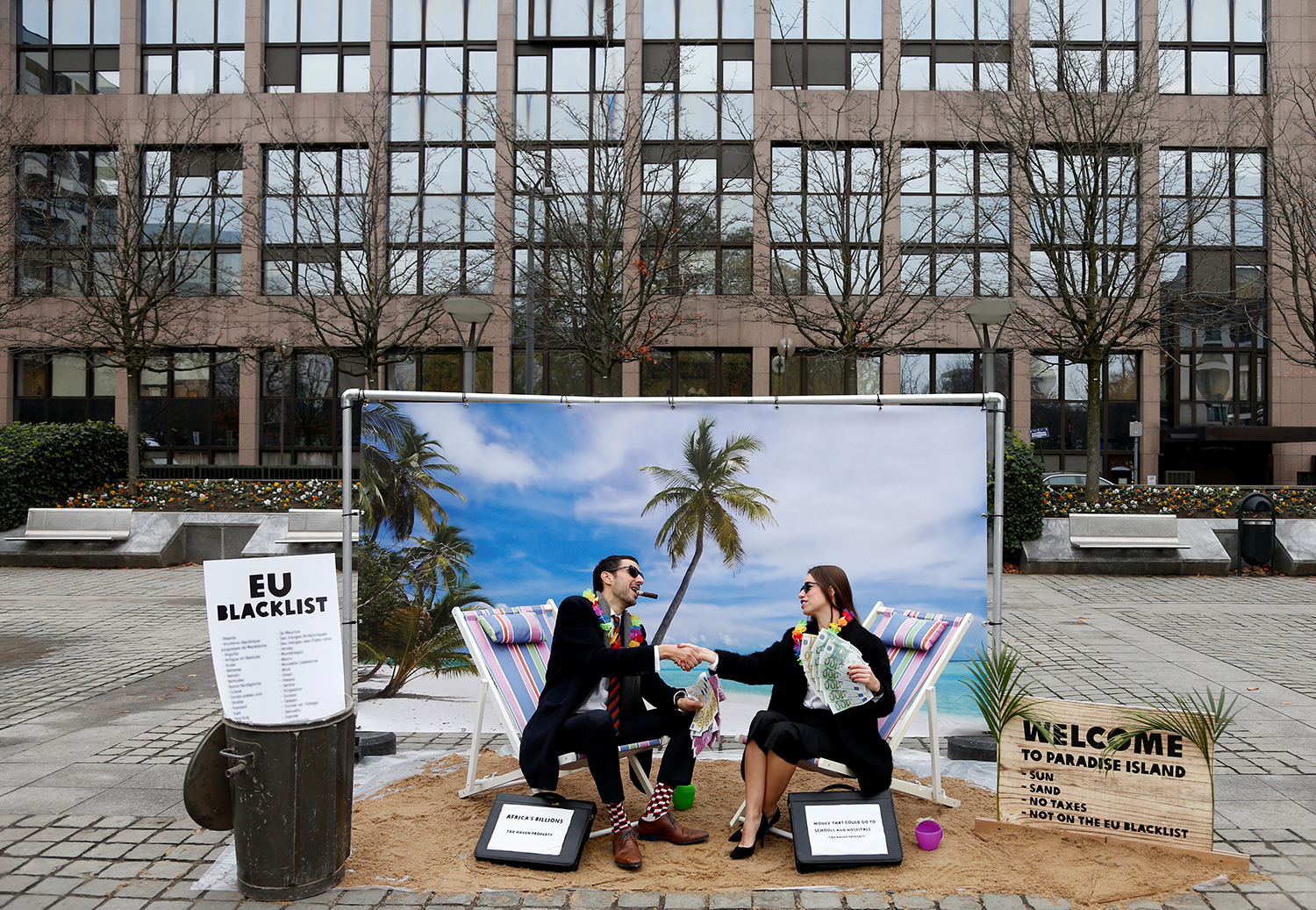 Activists stage a protest on a mock beach representing a tax haven outside a meeting of European Union finance ministers in Brussels, Belgium, on Dec. 5, 2017.