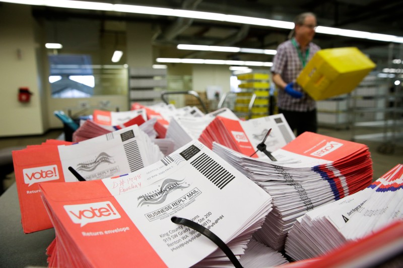 Empty envelopes of opened vote-by-mail ballots for the presidential primary are stacked on a table at King County Elections in Renton, Washington on March 10, 2020.