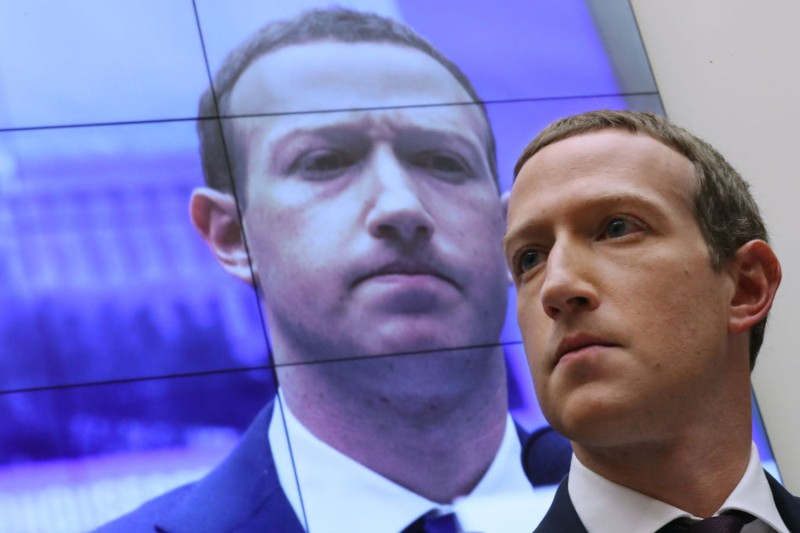With an image of himself on a screen in the background, Facebook co-founder and CEO Mark Zuckerberg testifies before the House Financial Services Committee in the Rayburn House Office Building on Capitol Hill October 23, 2019 in Washington, DC.