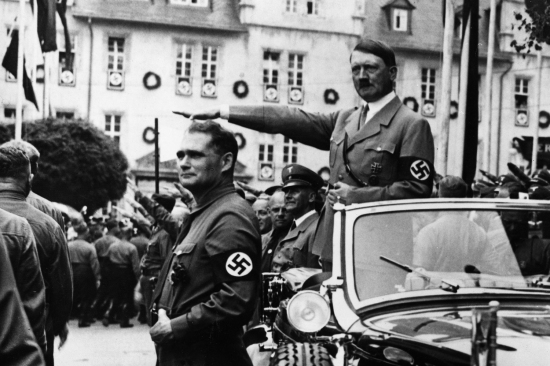 Adolf Hitler and his deputy Rudolf Hess take the salute at a prewar Nazi Party parade in Weimar, Germany, circa 1933.