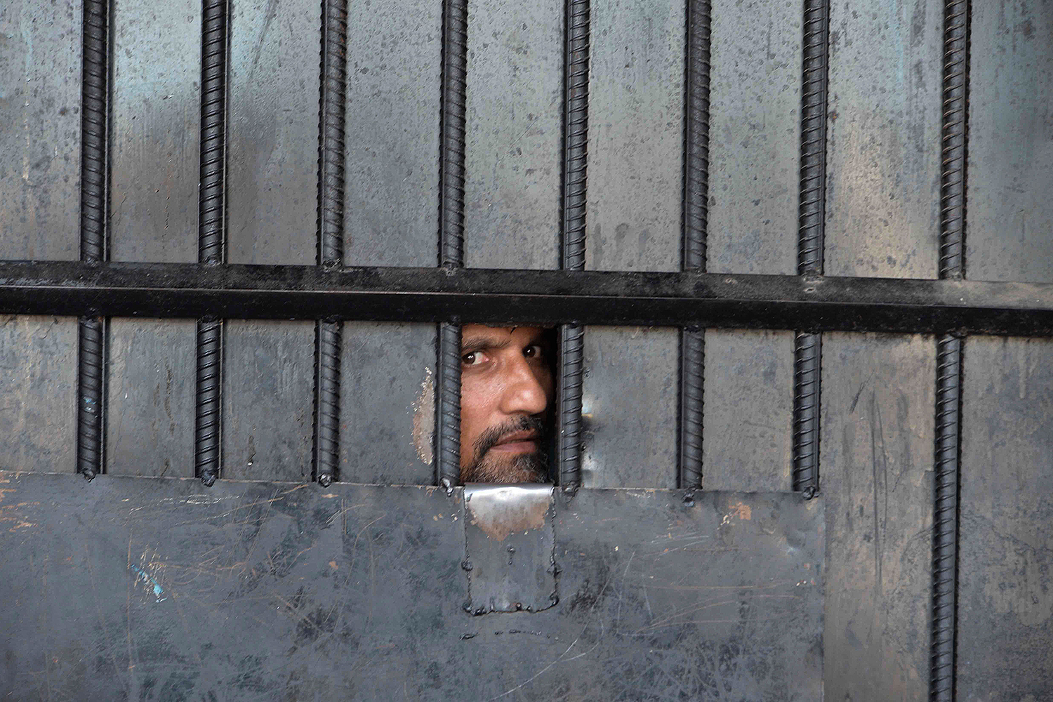 An inmate watches from behind a gate after a raid at the prison in Jalalabad, Afghanistan, on Aug. 3. The attack at the prison by gunmen, which left 29 people dead and officials looking for hundreds of escaped prisoners, was claimed by the Islamic State. NOORULLAH SHIRZADA/AFP via Getty Images