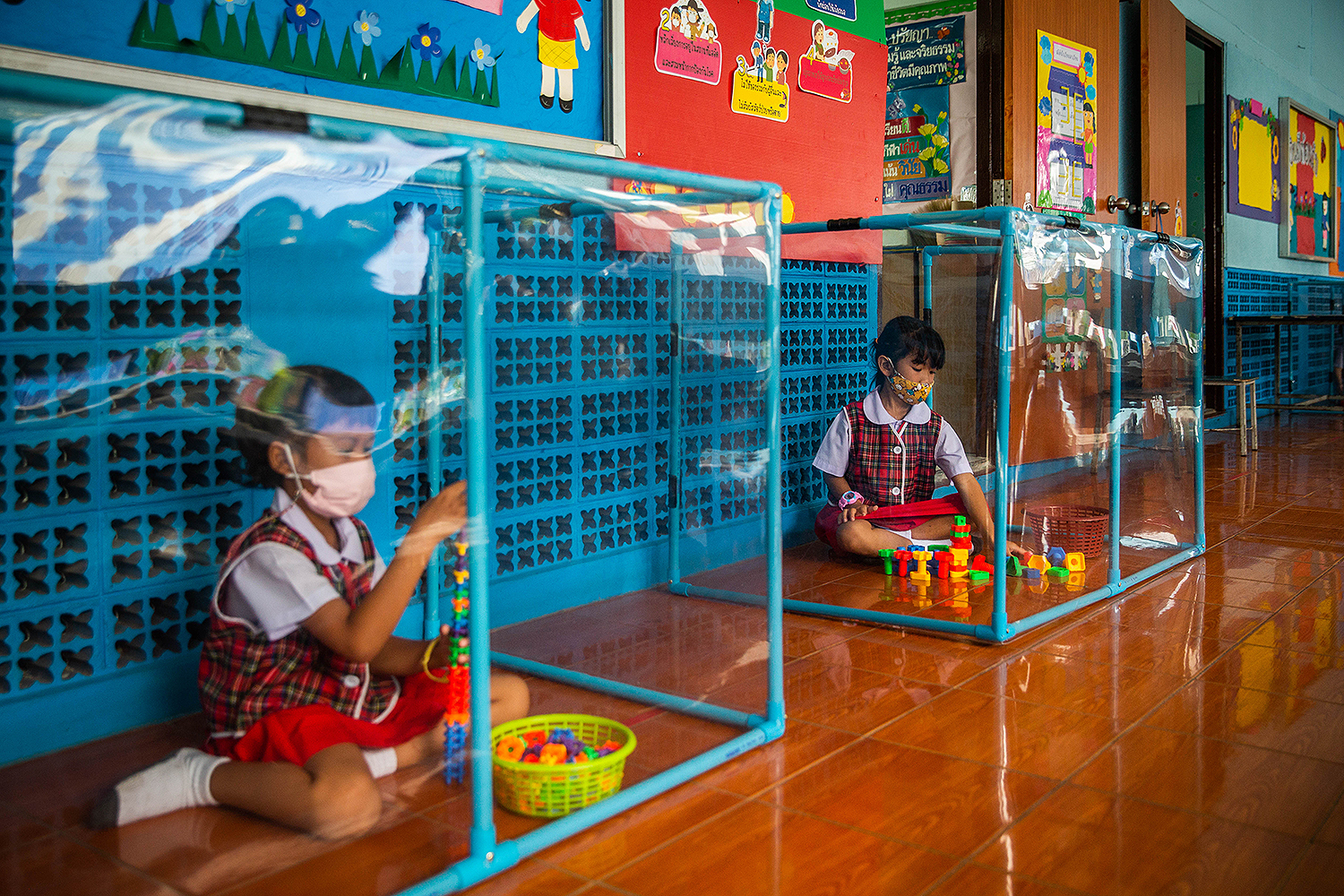 Kindergarteners wear face masks as they play by themselves in screened-in areas at the Wat Khlong Toey School in Bangkok on Aug. 10. In early July, the school reopened its doors after being closed since March because of the COVID-19 pandemic. Lauren DeCicca/Getty Images