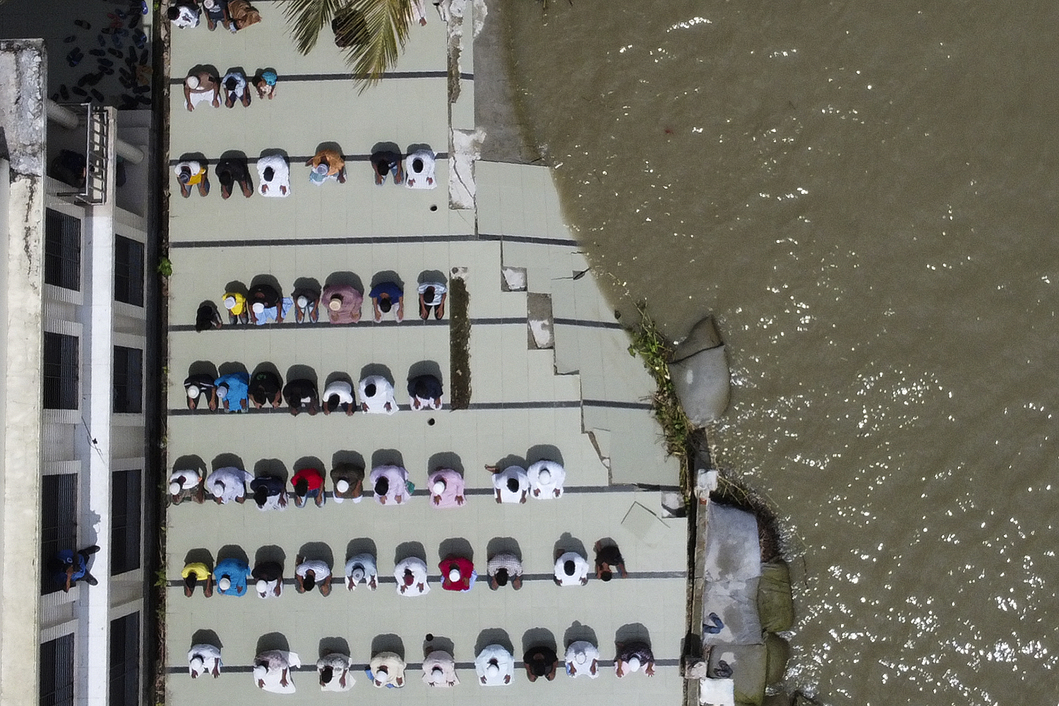 Muslim devotees offer Friday prayers outside a mosque whose yard was damaged by river erosion in Munshiganj, on the outskirts of Dhaka, Bangladesh, on Aug. 7. MUNIR UZ ZAMAN/AFP via Getty Images