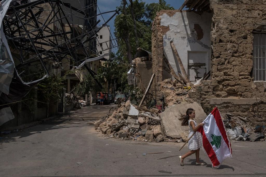 A girl carries a Lebanese flag through Beirut's Mar Mikhael neighborhood on Aug. 13.