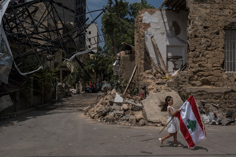 A girl carries a Lebanese flag through Beirut's Mar Mikhael neighborhood on Aug. 13.