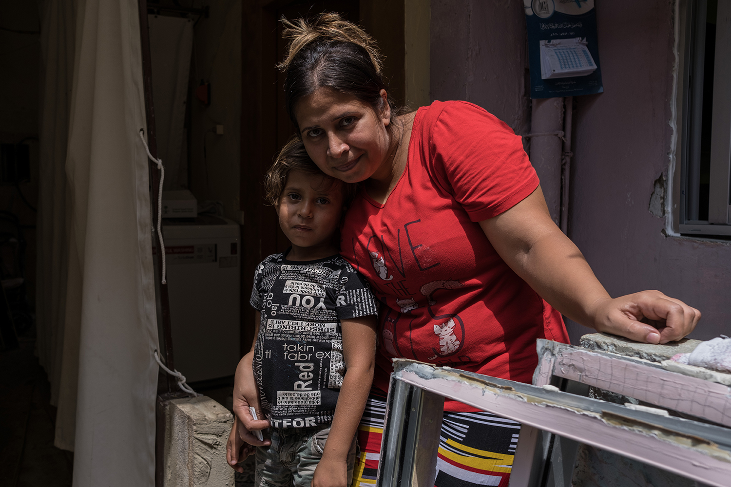 Khadije Hussain stands with her son Ali in front of her house in Beirut on Aug. 10, her hand resting on window frames that were blown out during the port explosion.