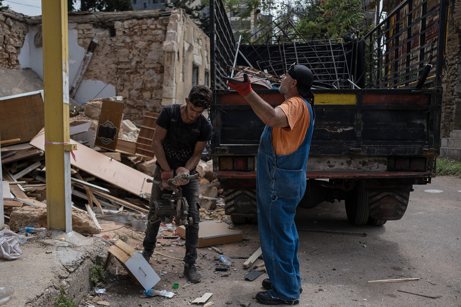 Vasken Mamoriyan (right) loads rubble from his home onto a truck in Beirut on Aug. 13.