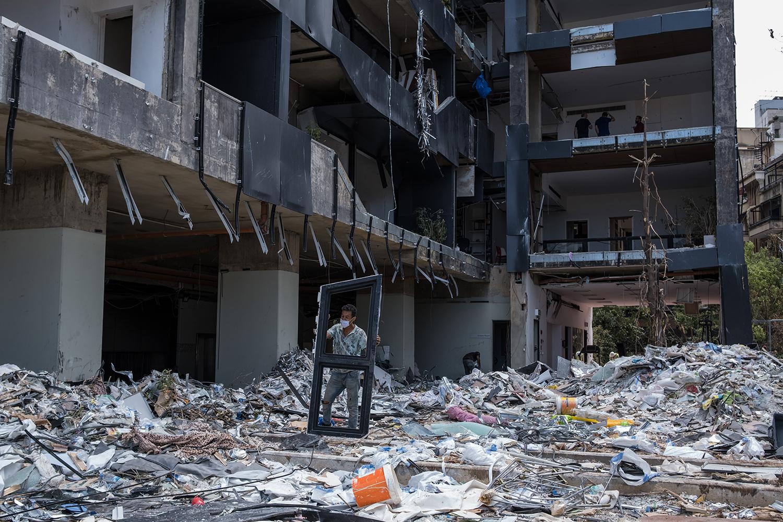 A man clears debris in blast-hit Beirut on Aug. 21.