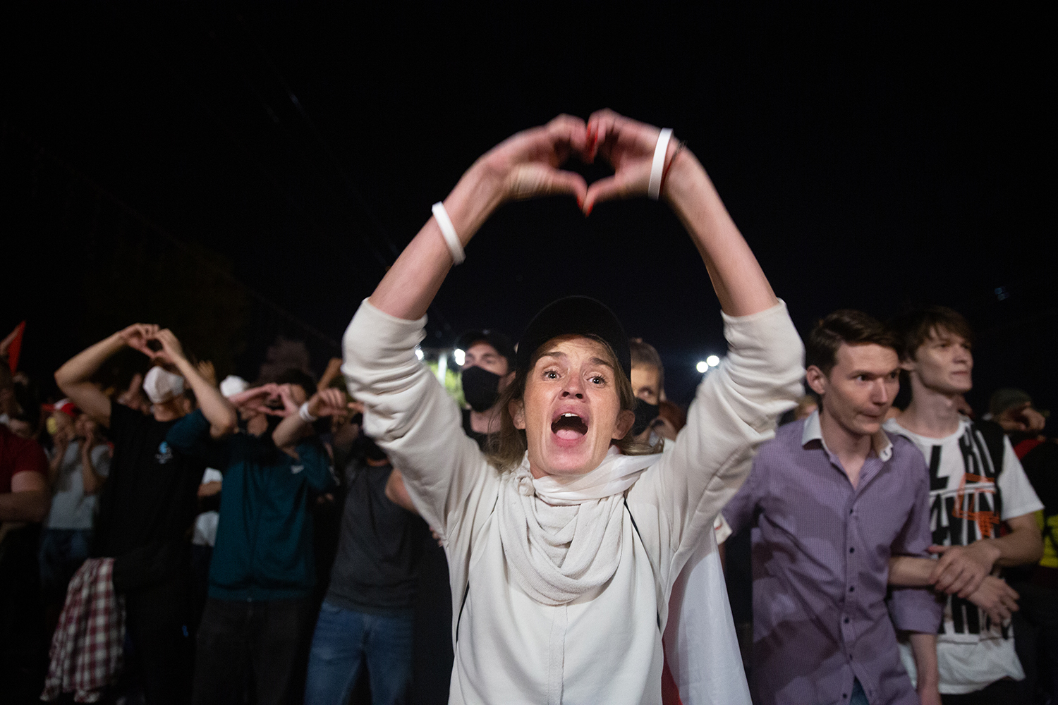 A woman raises her hands to form a heart—the symbol demonstrators have used to show their peaceful intentions—and begs police to put down their weapons and join protesters in Minsk on Aug. 9.