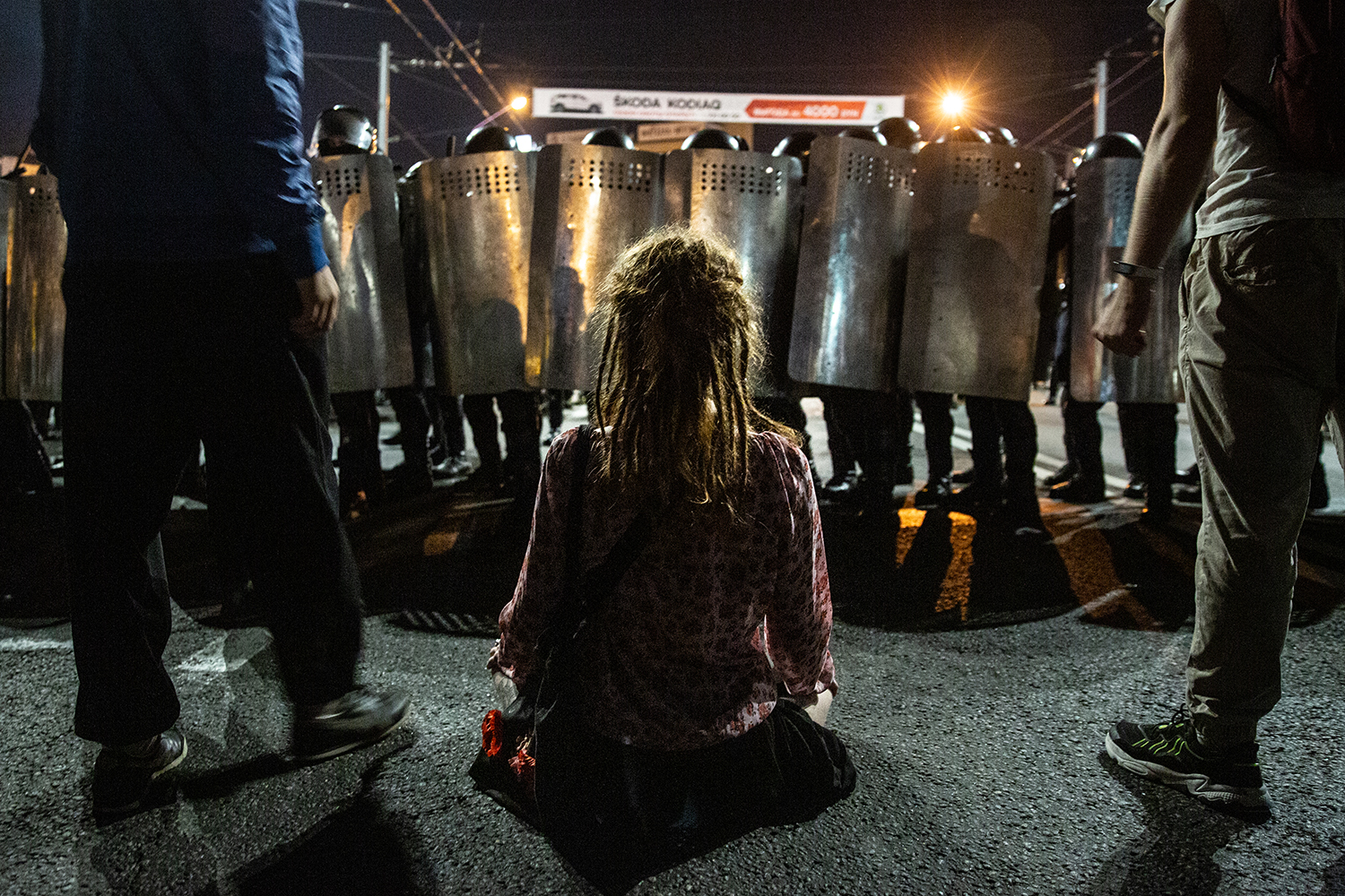 A woman sits in front of riot police as thousands march on Minsk to voice their anger at the contested election of Alexandr Lukashenko and his government on Aug. 9.