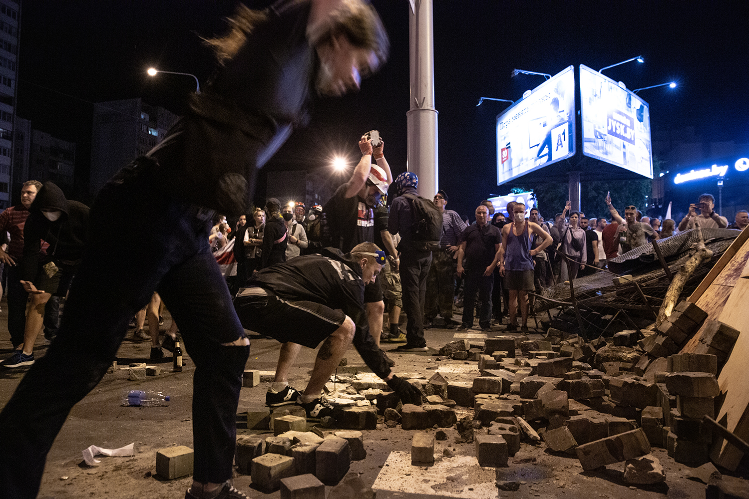 Protesters smash bricks into smaller pieces for ammunition to throw at riot police during a second night of protests after the election in Minsk on Aug. 10.