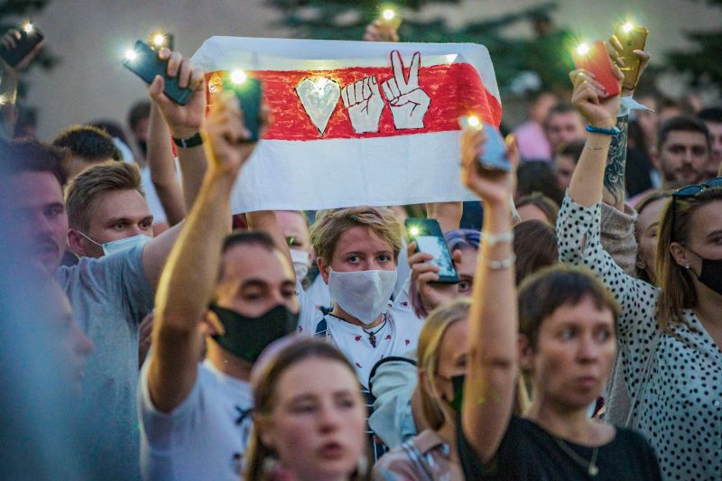 A woman holds a poster depicting the icons of the Belarusian opposition politician Svetlana Tikhanovskaya's presidential campaign at an unofficial rally in the capital of Minsk on Aug. 6.