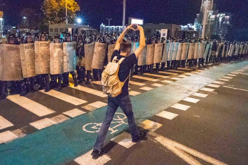 A protester walks in front of riot police making a heart gesture with his hands, one of the symbols used by the leading opposition candidate, Svetlana Tikhanovskaya, in Minsk, Belarus, on Aug. 9.