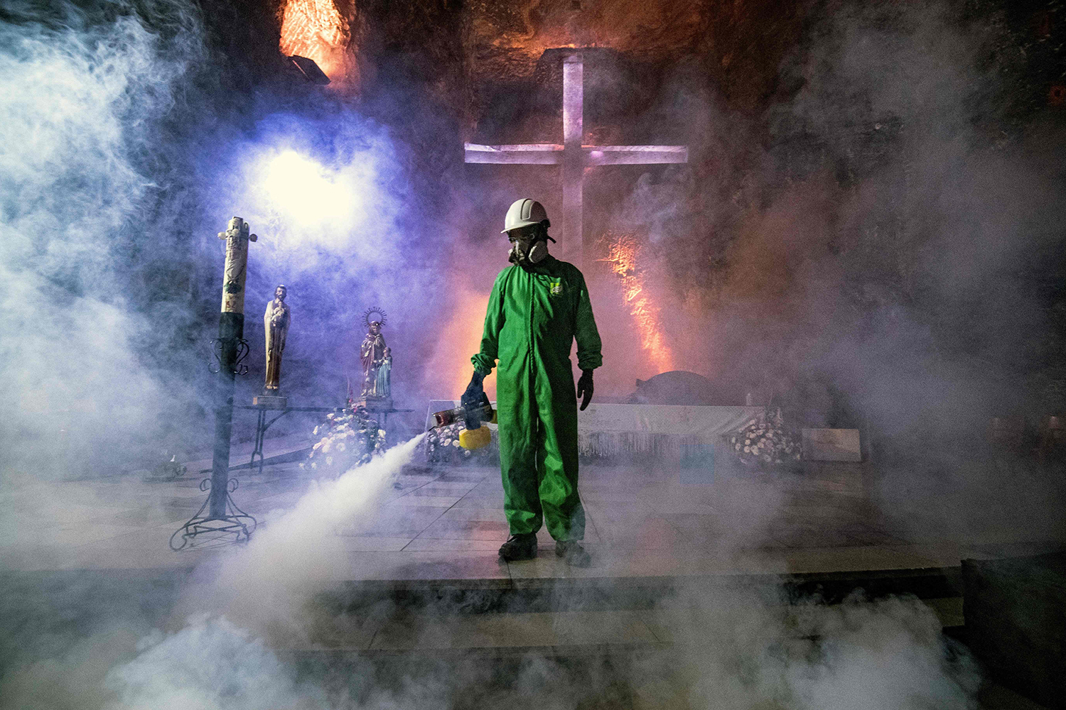 A worker disinfects the Salt Cathedral of Zipaquira, an underground church built into a salt mine, in Zipaquira, Colombia, on Aug. 30. The Salt Cathedral, one of Colombia's main tourist attractions, is waiting for an authorization from the Health Ministry to reopen in the midst of the pandemic. JUAN BARRETO/AFP via Getty Images