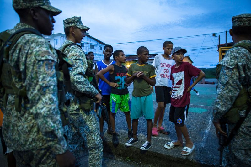 Children talk with soldiers in a municipality of Chocó, Colombia, on June 9, 2017. The area has grown used to the sight of heavily armed soldiers and continues to see swarms of villagers displaced by clashes between armed groups.