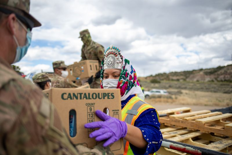 Miss Navajo Nation Shaandiin P. Parrish grabs a box filled with food and other supplies to distribute to Navajo families in Counselor on the Navajo Nation Reservation, New Mexico, on May 27.